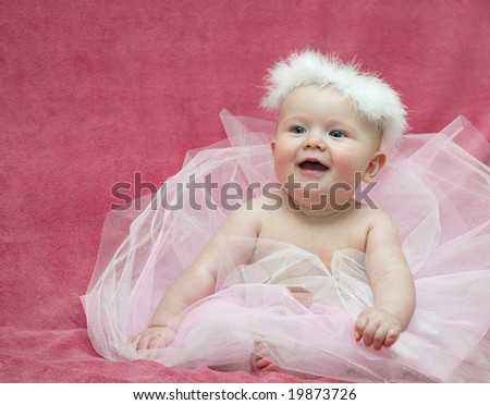 little baby girl ballerina sitting on pink background smiling