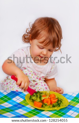 little baby girl eating by itself broccoli and carrot using a fork isolated on white