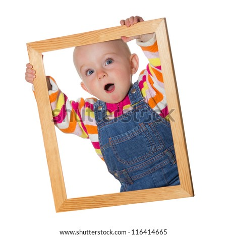 Little baby girl holding up an empty wooden picture frame around her face with a look of amazement isolated on white