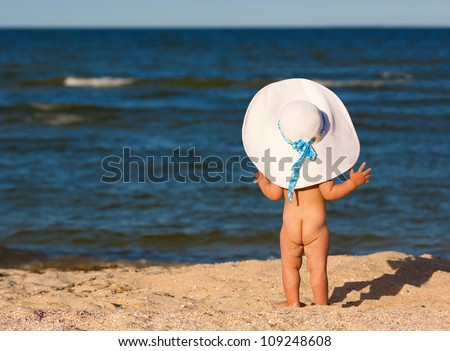 Little baby girl in big hat on the beach looking at sea