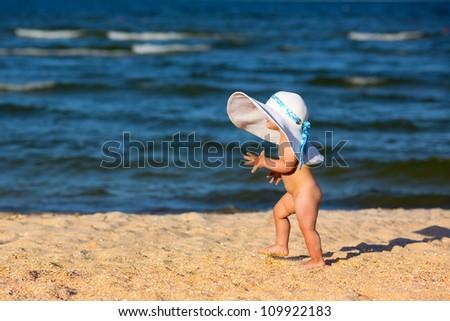 Little baby girl in big hat walking on the beach