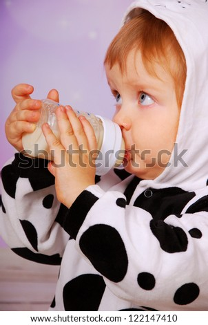 little baby girl in cow costume drinking milk from bottle