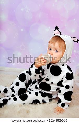little baby girl in cow costume drinking milk from bottle