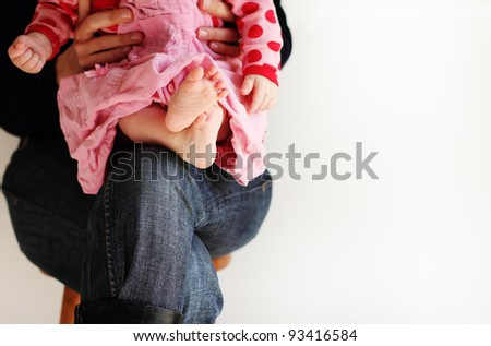 little baby-girl in pink dress sitting on her mother's hands