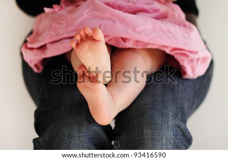 little baby-girl in pink dress sitting on her mother's hands - stock photo