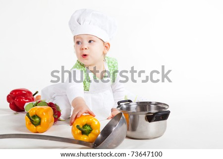 Little baby girl in the cook costume sitting near pan and vegetables.