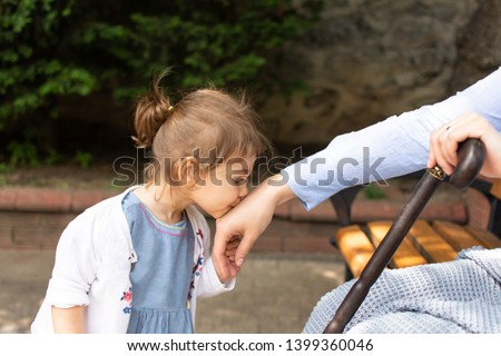 Little baby girl kiss her grandmother's hand during Eid mubarak (Turkish Ramazan or Seker Bayram). Adorable child kiss elderly woman hand to show respect. Cute toddler follow muslim Ramadan traditions