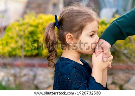 Little baby girl kiss her grandmother's hand during Eid mubarak (Turkish Ramazan or Seker Bayram). Adorable child kiss elderly woman hand to show respect. Cute toddler follow muslim Ramadan traditions