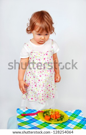 little baby girl looking sadly on a plate with  broccoli and carrot