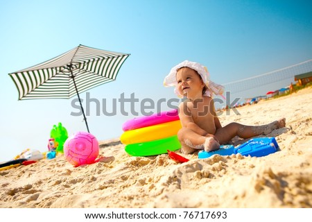 Little baby girl on the sand beach with beach toys