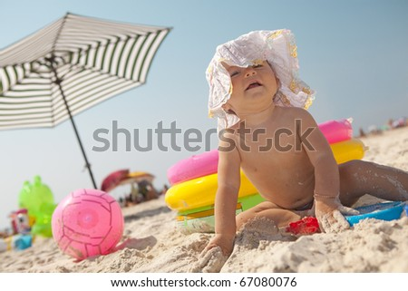 Little baby girl on the sand beach with hat and beach toys