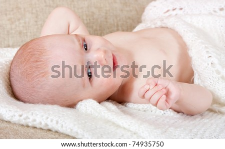 Little baby girl on white in home interior