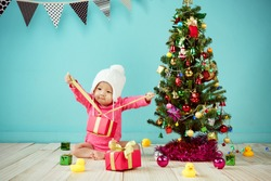Little baby girl open the gift box with decorating christmas tree on green background in winter season, Baby healthy and winter concept