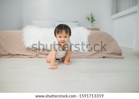 Little baby girl or girl crawling on floor in bed room