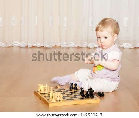 Little baby girl playing chess on the floor at home