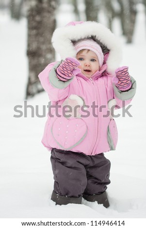 Little baby girl playing in a snowy winter park
