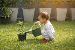 Little baby girl playing in green summer garden on sunny morning.