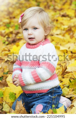 little baby girl playing with  autumn leaves