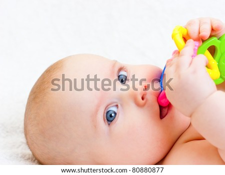 Little baby girl playing with teething toy - stock photo