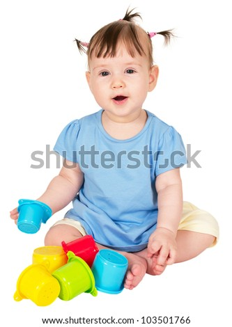 Little baby girl playing with toy stacking cups isolated on white background