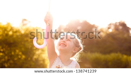 Little baby girl reaches for the sun's rays walking stick