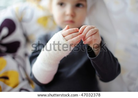 Little baby girl showing her bandaged hand