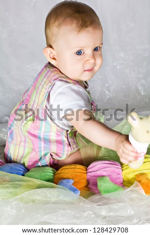 Little baby girl sitting and playing with toys