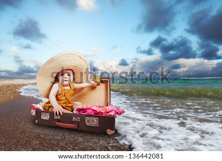 Little baby girl  sitting into retro suitcase at the sea coast