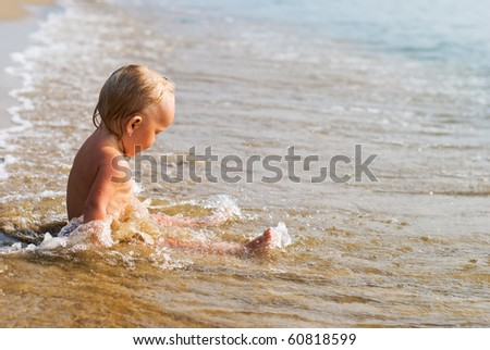 Little baby girl sitting on the beach and playing in waves.