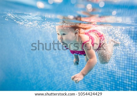 Little baby, girl swimming under water in paddling pool. Diving baby. Learning infant child to swim. Enjoy of swimming and bubbles.