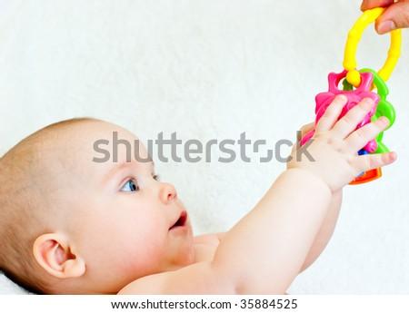Little baby girl taking teething toy
