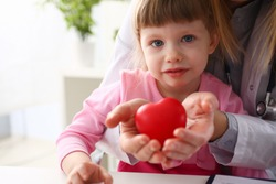 Little baby girl visiting doctor holding in hands red toy heart as life safe symbol