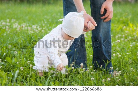 Little baby girl walking in a summer park with her father
