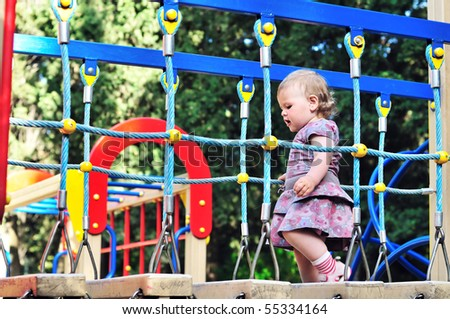 Little baby girl walking on playground in the park