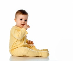 Little baby girl wearing yellowe jumpsuit scratching first teeth growing in gum with hand finger sitting on floor studio shot. Full length portrait isolated on white copy space. Teething concept