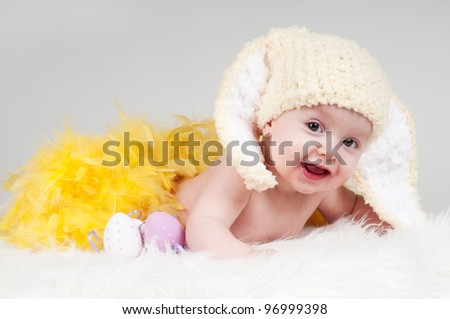 little baby girl with bunny ears and yellow feathers