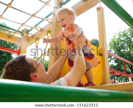 Little baby girl with her father on playground