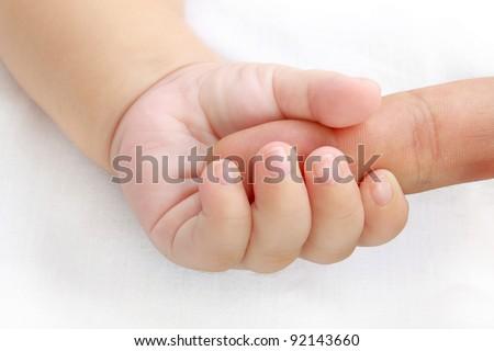 little baby hand holding a mother's finger