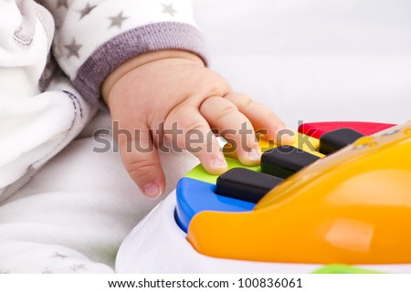 little baby hand pianist plays on a colorful toy piano