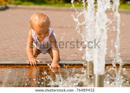 Little baby holds hands over fountain and laughs.