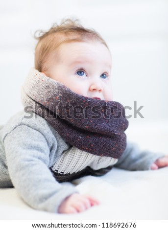 Little baby in a frey knitted sweater and big brown scarf