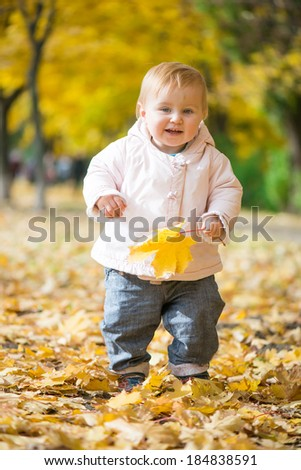 little baby in the park with golden autumn leaves
