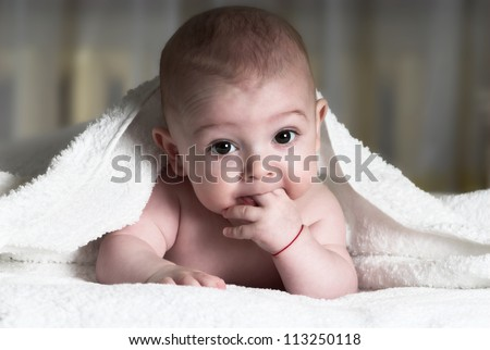 Little baby is lying in bed with fingers in mouth