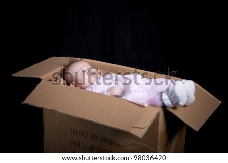 Little baby is posing in box.