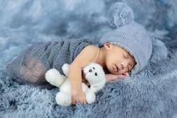 Little Baby lying down hugging a teddy bear.