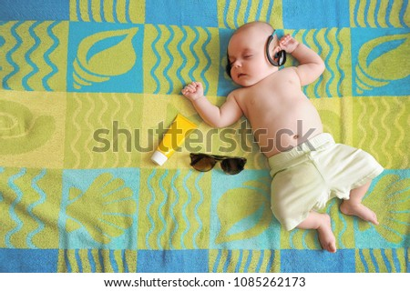 Little baby lying on a big beach towel with sunscreen cream and sun glasses next to him, listening to relaxing music in his dad's wireless headphones. Sun safety tips for babies, infants and toddlers
