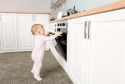 Little baby near stove in kitchen. Child in danger
