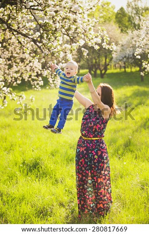 little baby on hands of mother. woman playing with child outside in blooming spring garden. portrait of family of two people. happy family concept. spring landscape background. apple trees in blossoms