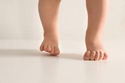 Little baby on light background, closeup on feet