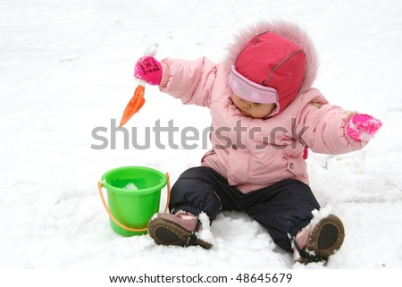 Little Baby Playing with Snow in Winter Outdoors